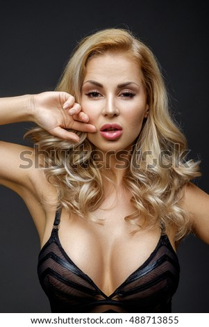 Very beautiful sexy blonde woman posing in studio over grey background, looking at camera.