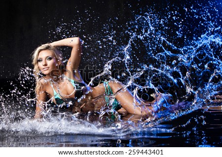 Very beautiful sexy girl blonde in black and blue swimsuit on the background of flowing water and water spray in the Studio on a dark background with blue back light - stock photo