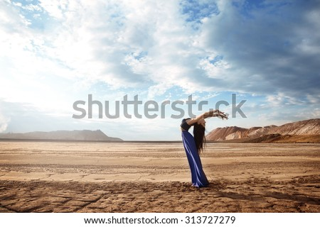 Very beautiful slim girl with long black hair in a long blue dress is posing in the desert near the mountains - stock photo