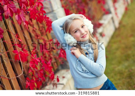 Very beautiful toddler blond girl posing in autumn garden with red plant - stock photo