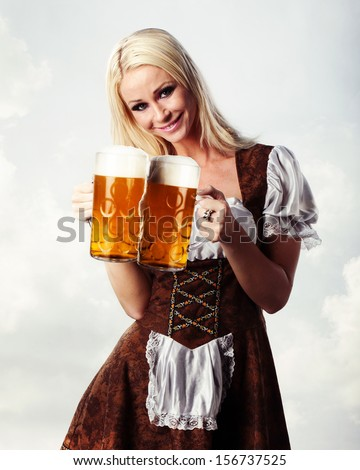 very beautiful woman in tiroler oktoberfest dress or dirndl is holding a big glass of beer in her hands