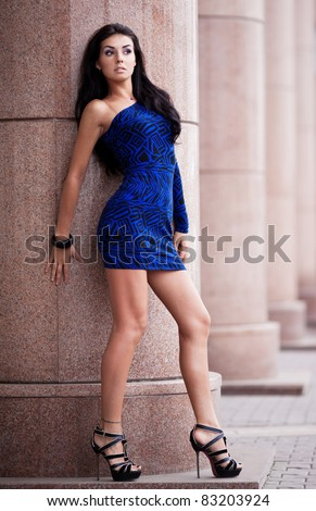 very beautiful young brunette woman wearing a blue mini dress in the street - stock photo