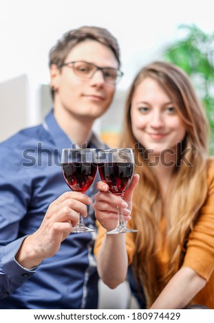Very beautiful young couple toasting wine glasses - stock photo