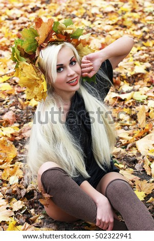 Very beautiful young girl in autumn park with wreath of leaves. Close-up. Girl on a background autumn leaves. Autumn. Beautiful make-up