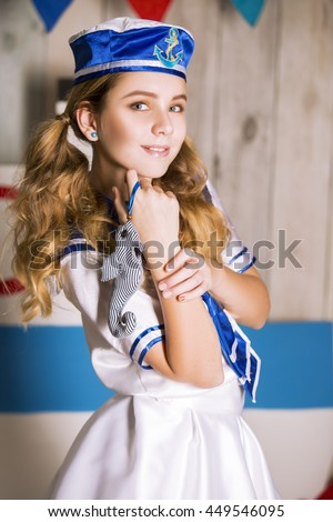 very beautiful young girl with her chic hair tresses blond curls with sound around blonde hair white dress flirts sailors beautiful eyes Teen Cutie hand look weird - stock photo