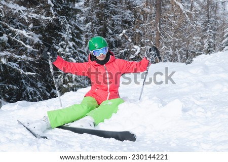 Very beautiful young woman wearing red jacket and green pants skiing in the Alps