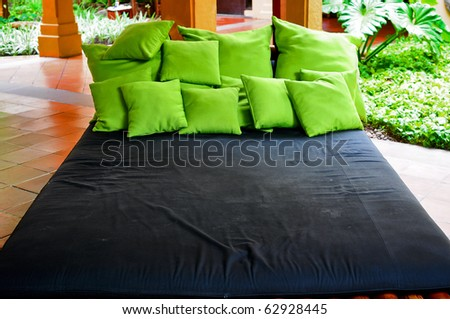 Very big bed with many green pillows - stock photo