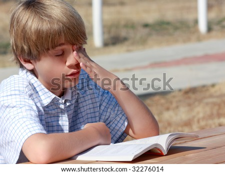 Very bored teenager at an outside table trying to read. - stock photo
