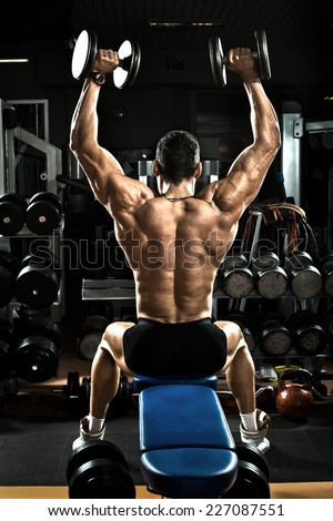 very brawny guy bodybuilder,  execute exercise with  dumbbells, on deltoid muscle shoulder - stock photo