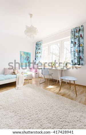 Very bright and airy room with light furniture, subtle decorations and large fluffy carpet in the foreground
