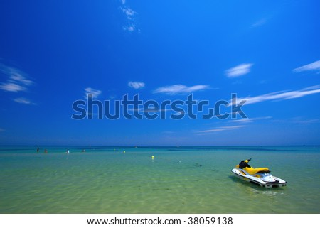 Very bright day, beautiful clear water, clear wave breaking into shore. Bright blue sky, minimal cloud cover. Tunis.