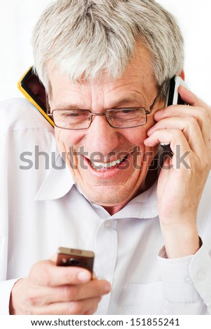 Very busy older man using a few phones in same time - stock photo