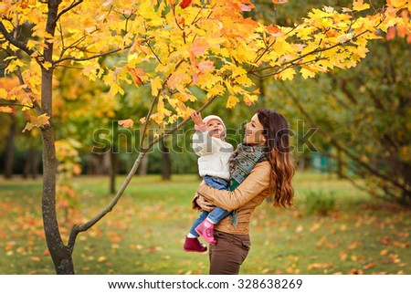 Very charming beautiful brunette mom in a brown jacket holding a little girl her daughter and smiles happily on the background of yellow leaves of maple in autumn - stock photo