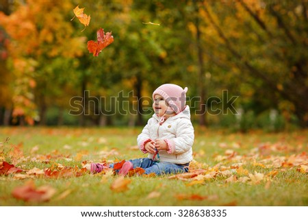 Very charming beautiful little girl with big brown eyes and pink hat sitting on the grass on a background of yellow maple leaves in autumn - stock photo