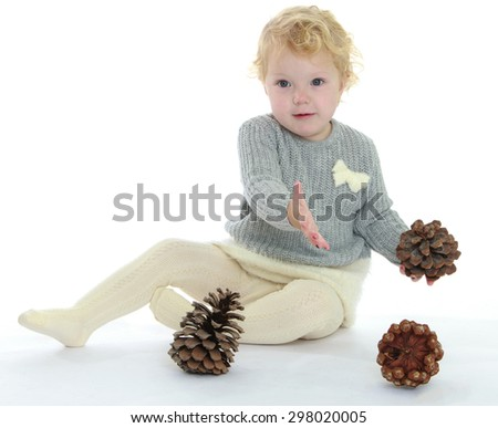 Very charming little girl playing with large pine cones sitting on the floor-Isolated on white background