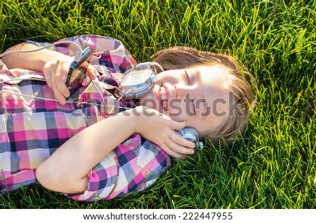 Very cheerful and funny little girl listening to music in the green grass. - stock photo