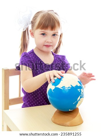 very clever little girl sitting at a table in the Montessori classroom. - stock photo