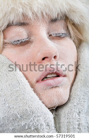 Very cold weather. Close-up portrait of chilled female face covered in ice. - stock photo