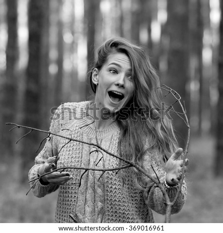Very crazy,surprised,amazed,mad,yelling,screaming,attractive,beautiful,funny,nice,frustrated,angry,shouting,furious,stressed girl in the dark forest with a brunch of dry tree.Black and white photo. - stock photo