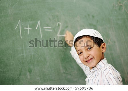 Very cute and positive kid smiling and writing on school board - stock photo