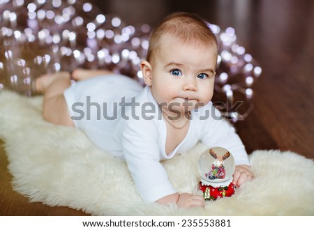 Very cute baby lying on the floor on the background lights near the Christmas ball - stock photo