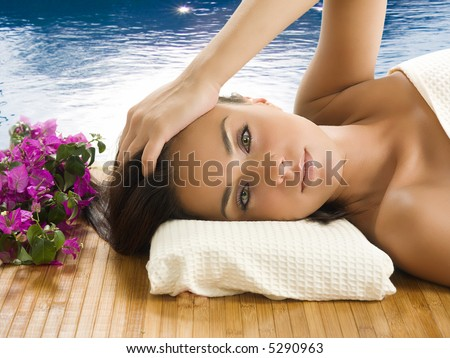 very cute brunette with wonderful eyes laying down on a carpet near a swiming pool