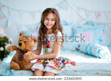 Very cute curly haired young girl sitting on the bed with soft toy - stock photo