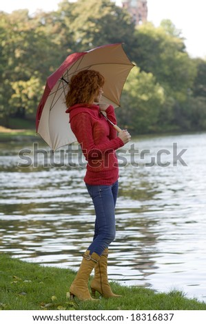 very cute girl looking river with colored umbrella and red pullover