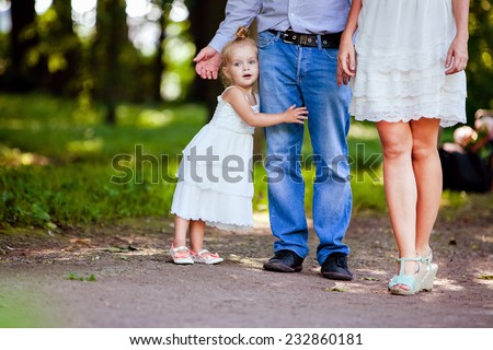 very cute little blonde girl holding the foot mom and dad - stock photo