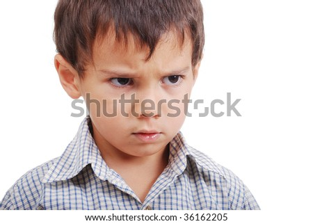 Very cute little boy with angry expression on face - stock photo
