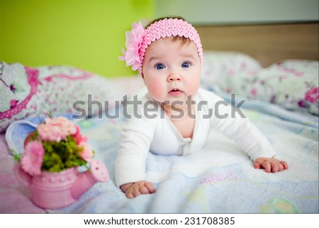 very cute little girl lying on the bed, leaning on the handle - stock photo