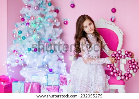 Very cute long-haired young girl with blue eyes sitting on a chair against a white Christmas tree - stock photo