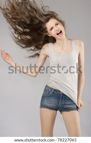 very cute young girl in casual dress screaming with her long hair in wind - stock photo