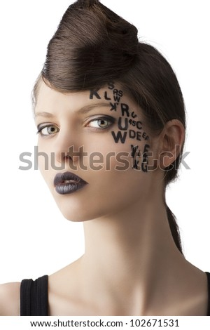 very cute young girl with letter and number painted on her face and a nice creative hair style, she is turned of three quarters at right and looks in to the lens