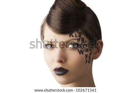 very cute young girl with letter and number painted on her face and a nice creative hair style, she looks in to the lens