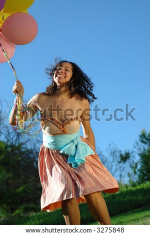 Very cute young woman having a blast of a birthday in a vintage dress with a bunch of colorful balloons in tow. - stock photo