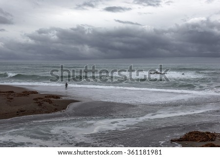 Very dark stormy overcast day. El Nino weather storm floods Central California Coast beach, with powerful wind, rain, waves, & heavy surf, near Cambria, CA. on the Big Sur Coast. - stock photo