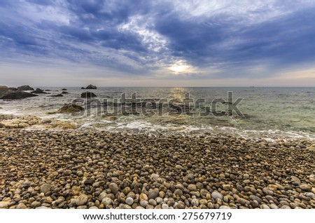 Very dramatic sunset on the rocky shore of the sea. amazing seascape - stock photo