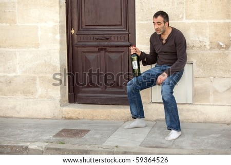 very drunk man standing near house door in the city - stock photo