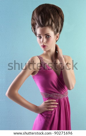 very elegant young woman wearing a pink evening dress and fashion up-do on turquoise background - stock photo