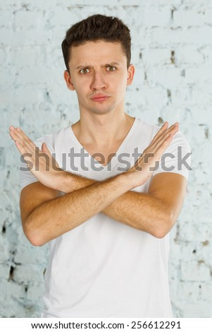 Very emotional man. Modern young man. Mimicry of his face shows what he is going through. Show gesture with his hands. Gesture stop, no, you can not, ever. Put your hands in the shape of a cross. - stock photo