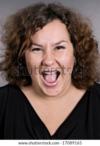 very emotional woman is screaming over grey background