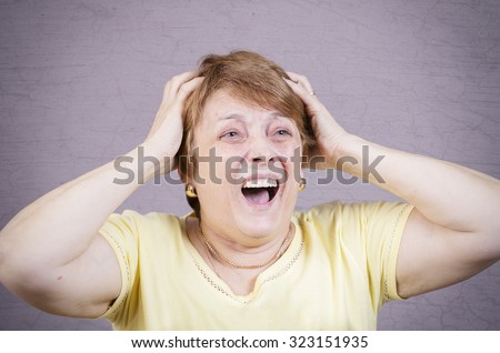 Very emotional woman screams on a gray background.