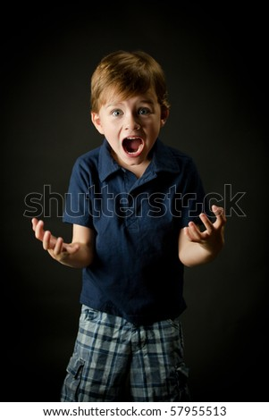 Very emotional young boy screaming with all his energy - stock photo