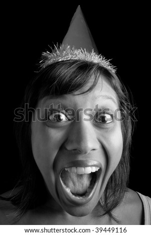 very excited Indian birthday girl in party hat, photographed in front of a black background
