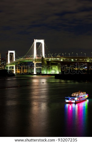 very famous Tokyo landmark, Tokyo Rainbow bridge over bay waters with scenic night illumination and traditional japanese boats