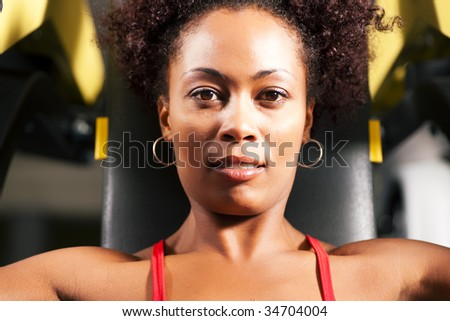 Very fit and beautiful african-american woman in a gym working out and lifting weights on an exercising machine - stock photo