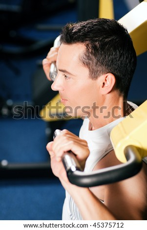 Very fit and handsome man in a gym exercising and lifting weights on an exercising machine - stock photo