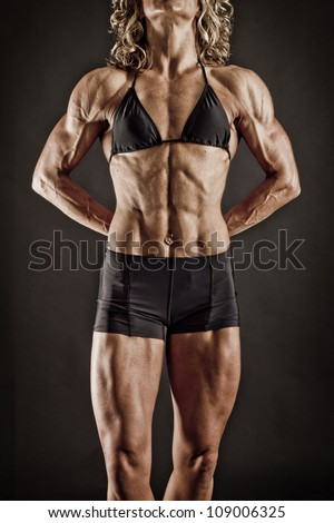 Very Fit and Toned Female BodyBuilder showing her Ads - stock photo