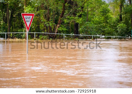 Very flooded road and give way sign in Queensland, Australia - stock photo